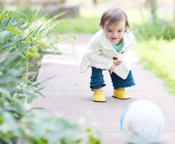 Child Plays with Ball in Yellow Leather Shoes